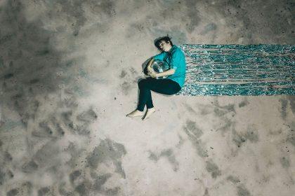 Zu sehen ist ein auf dem Fußboden liegender Mensch mit einer Diskokugel im Arm und blaues Lametta um sich