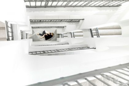 """Zu sehen ist ein weißes Treppenhaus mit zwei umschlungenen Menschen als Beitragsbild zu """"Aufzeichnungen aus dem kellerloch"""", Foto von Sebastian Schimmel"""
